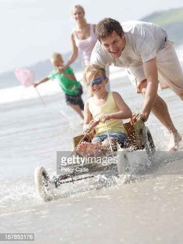 Family running on beach with hand made go-kart : Stock Photo