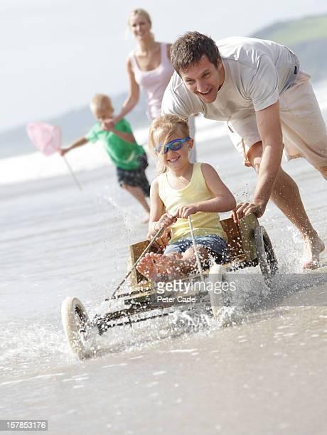 Family running on beach with hand made go-kart