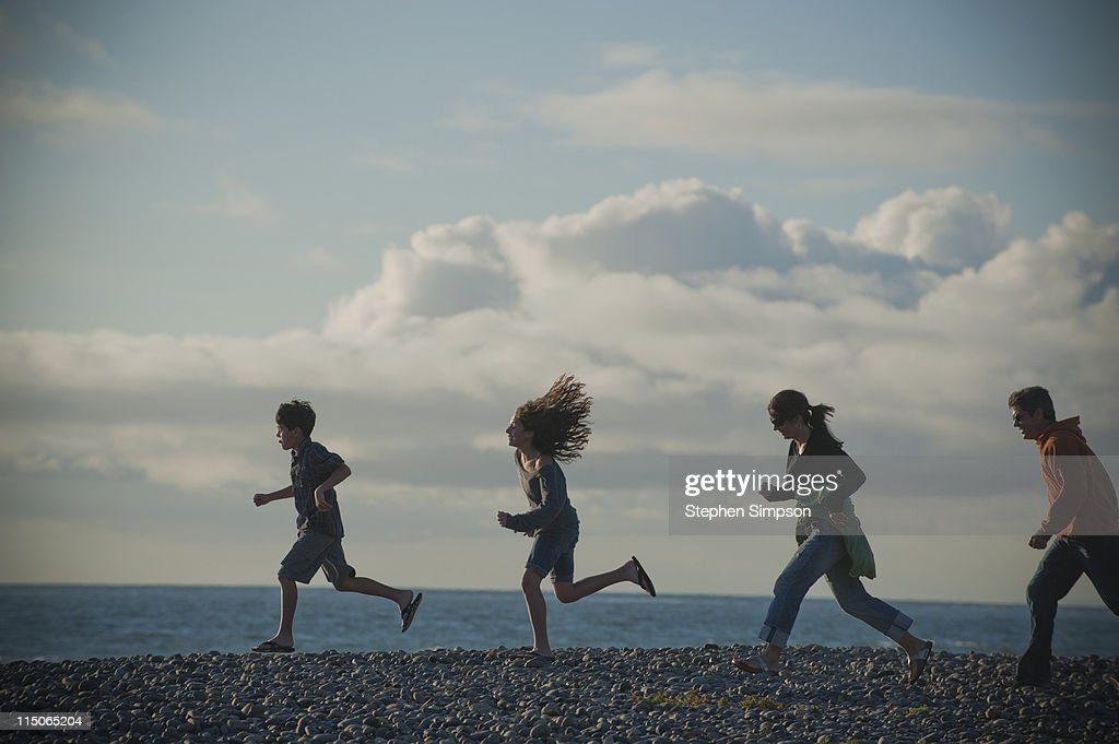 family running on cobblestone beach, sunny day : Stock Photo