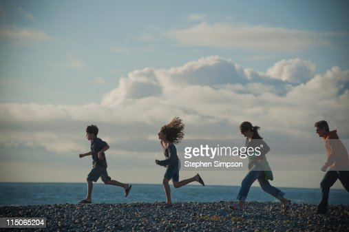 family running on cobblestone beach, sunny day : Stock Photo