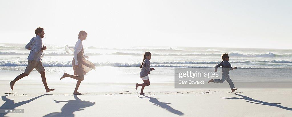 Family running on sunny beach : Photo