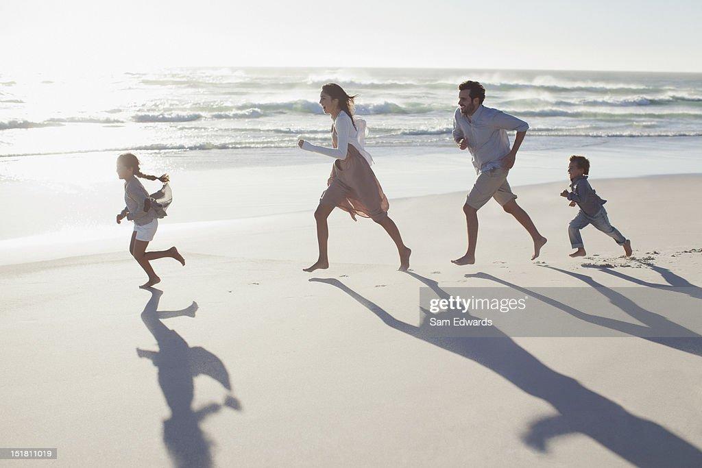 Family running on sunny beach : Stock Photo