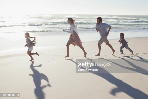 Family running on sunny beach : Stock Photo