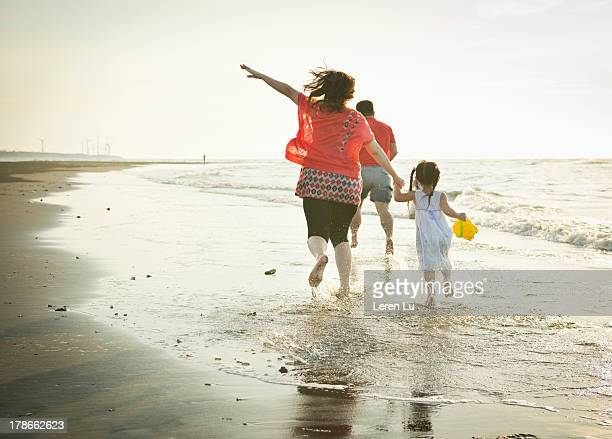 Family running on the beach happily