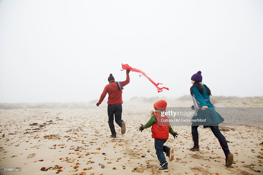 Family running on the beach with kite : Stock Photo