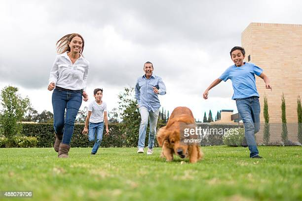 Family running outdoors with their dog