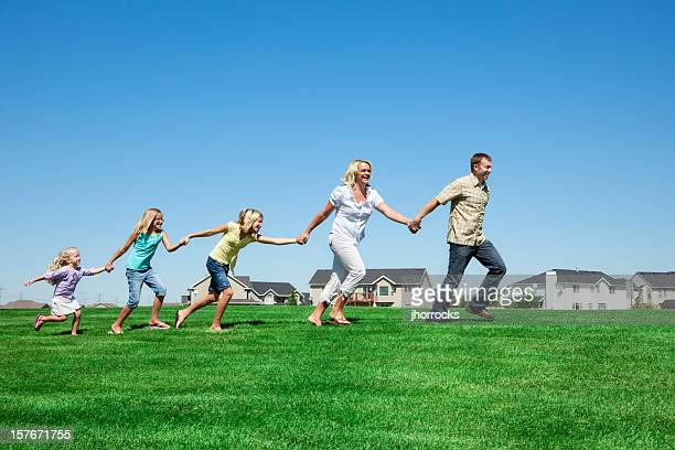 Family Running Through Neighborhood Park