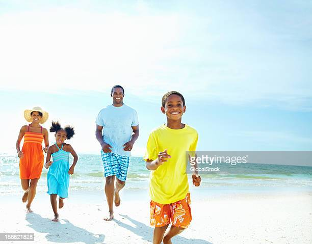 Family running together on the beach