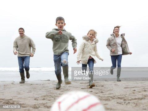 Family running towards ball on beach in winter