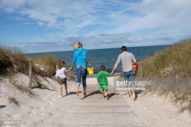family running towards the beach