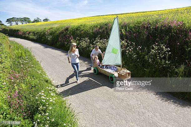 Family running with kart in country lane