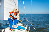 Mother and baby boy sail on yacht in sea. Family sailing on boat. Mom and kid in safe life jacket travel on ocean ship. Parent and child enjoy yachting cruise. Summer vacation. Sailor on sailboat.