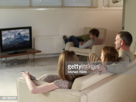 family sat on sofa at home watching TV
