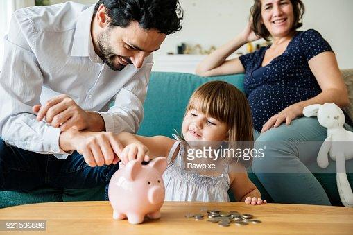 Family saving money in piggy bank : Stock Photo