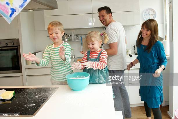 A little boy and a little girl baking a cake together Father and mother are in the kitchen and watch their children there Aachen