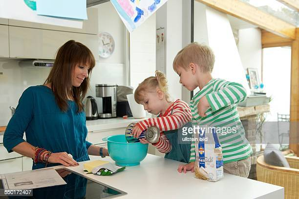 A mother bakes with her two children in kitchen making a cake The little girl throwing the flour from the measuring cup in a mixing bowl Her brother...