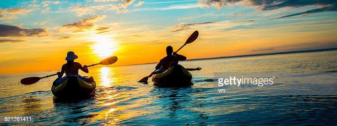 Famille faire du kayak en mer au coucher du soleil