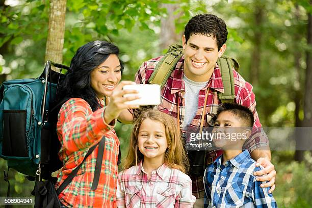 Family 'selfie' using smart phone to capture camping trip.