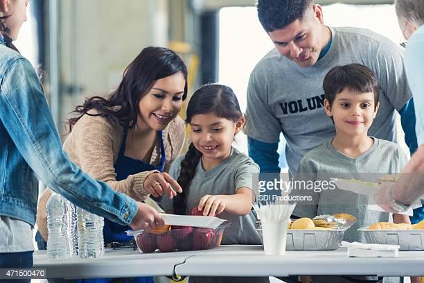Familie in der Küche, während Sie den Freiwilligen in Suppe Küche zusammen