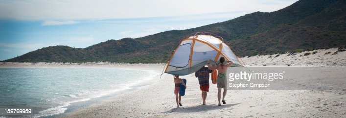 family setting up camp on wide empty beach : Stock-Foto