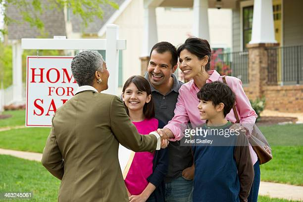 Family shaking hands with realtor at new house