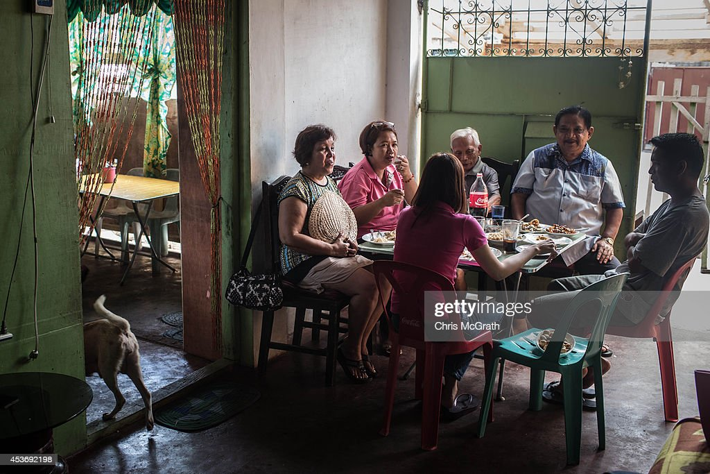 A family shares stories over Fiesta lunch during the Magallanes district Fiesta on August 16, 2014 in Tacloban, Leyte, Philippines. Fiesta is an annual celebration held by each town. The day generally starts with an early morning parade, before families gather at home for a large lunch often sharing the Philippine national food Lechon. (roast pork) Residents of Tacloban city and the surrounding areas continue to focus on rebuilding their lives nine months after Typhoon Haiyan struck the coast on November 8, 2013, leaving more than 6000 dead and many more homeless. With many businesses and government operations back up and running and with the recent start of the years typhoon season, permanent housing continues to be the main focus with many families still living in temporary accommodation. As well as continuing recovery efforts Leyte is preparing for the arrival of Pope Francis, who will visit the region from January 15- 19. on August 16, 2014 in Tacloban, Leyte, Philippines.