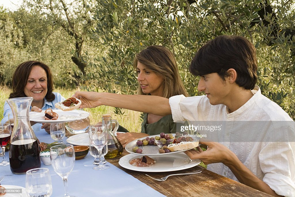 Family sharing Tuscan antipasto , Montevettolini , Italy : Stockfoto