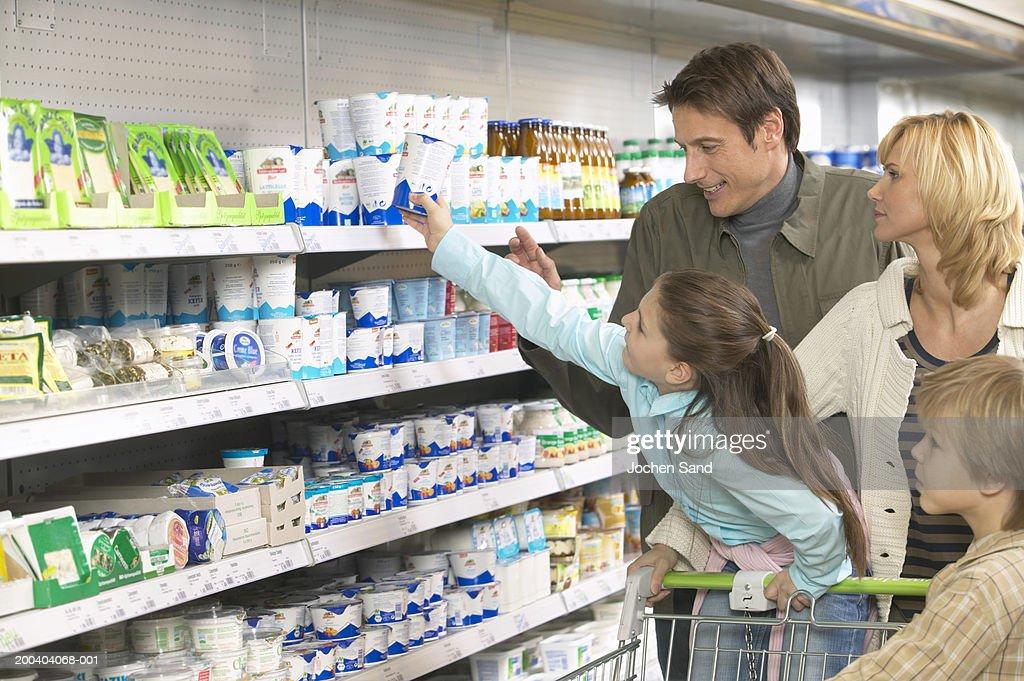 Family shopping in supermarket, girl (8-10) reaching for product on shelf : Stock Photo