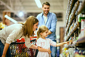 Family with one child shopping together in toy store.