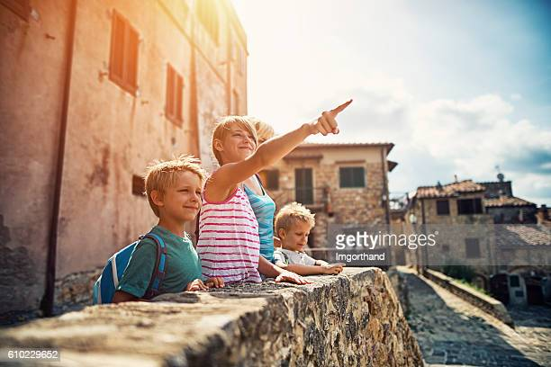 Family sightseeing charming little Italian town in Tuscany