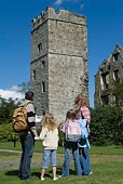 Family sightseeing in Ireland park viewing ruins of tower
