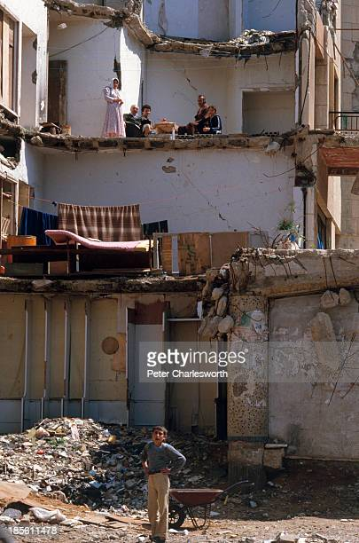 A family sit at a table unwittingly al fresco in what remains of their devastated apartment during a lull in fighting the facade of the building have...