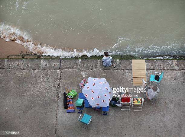 A family sit next to the sea on a concrete walkway at Louisa Bay on August 2 2011 in Broadstairs England Holiday makers packed the eastern corner of...