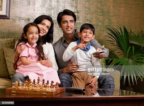 family sit on couch, chess set, big plant