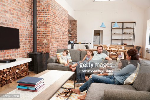 Family Sit On Sofa In Open Plan Lounge Watching Television : Photo
