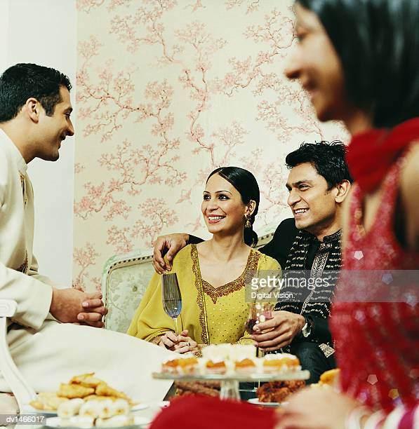 Family Sit Talking in Traditional Indian Dress