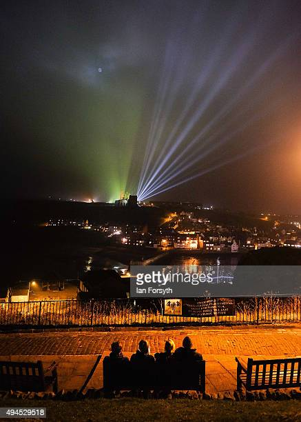A family sit watching as a spectacular light display illuminates the historic Whitby Abbey on October 27 2015 in Whitby England The famous...