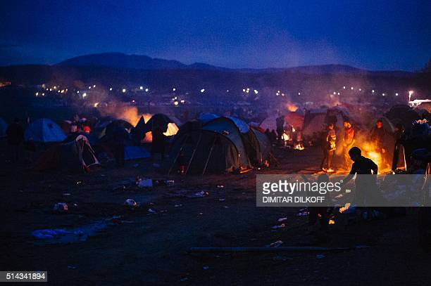 A family sits around a bonfire among other migrants and refugees at the makeshift camp of the GreekMacedonian border near the village of Idomeni on...