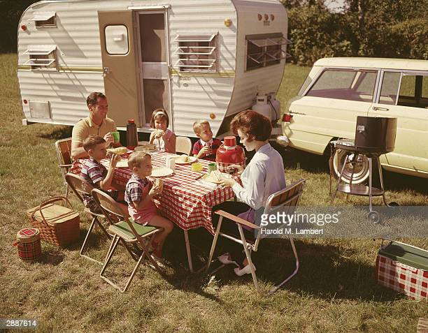 A family sits at a folding table eating a meal outside their station wagon and trailer circa 1963