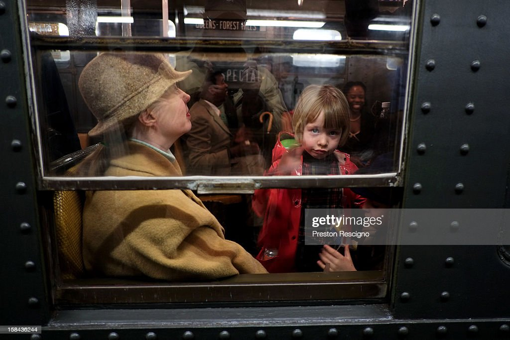 A family sits in a vintage New York City subway car on December 16, 2012 in New York City. The New York Metropolitan Transportation Authority (MTA) runs vintage subway trains from the 1930's-1970's each Sunday along the M train route from Manhattan to Queens through the first of the year.