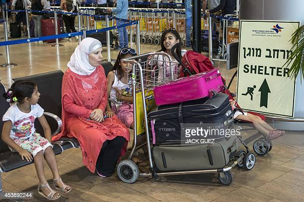 A family sits next to a sign directing passengers to a shelter at Ben Gurion International airport near the Mediterranean Israeli coastal city of Tel...
