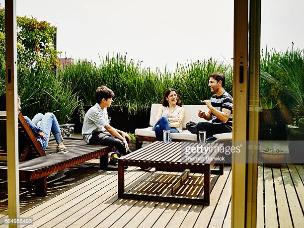 Family sitting and laughing together on terrace