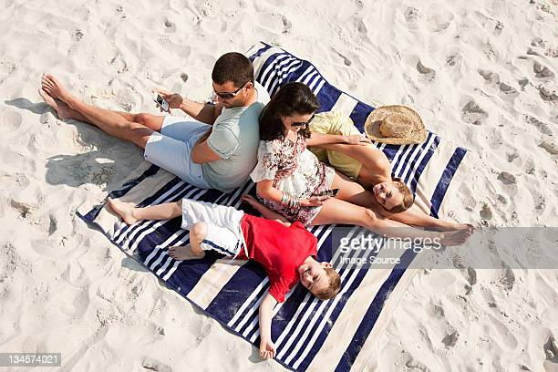 Family sitting and lying together on a rug on a beach