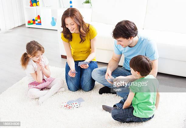 Family sitting and playing cards in living room