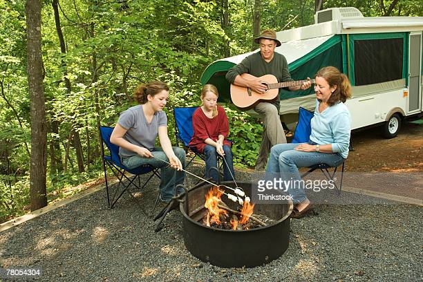 Family sitting around campfire