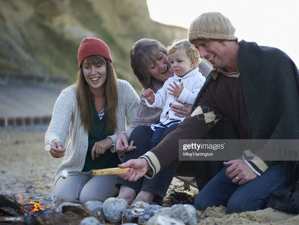 Family sitting around fire on beach : Stock Photo