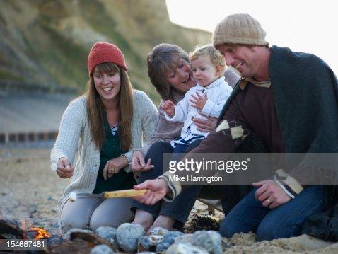 Family sitting around fire on beach : Foto de stock
