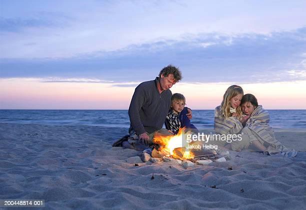 Family sitting around fire on beach, sunset