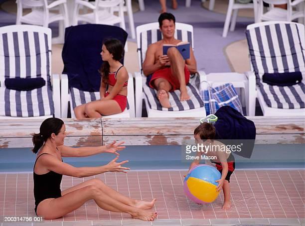 Family sitting around swimming-pool having fun