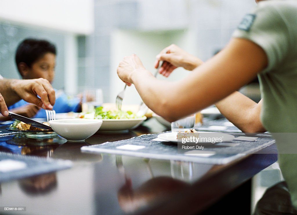 Family sitting around table eating dinner, womans arms in foreground : Stock Photo
